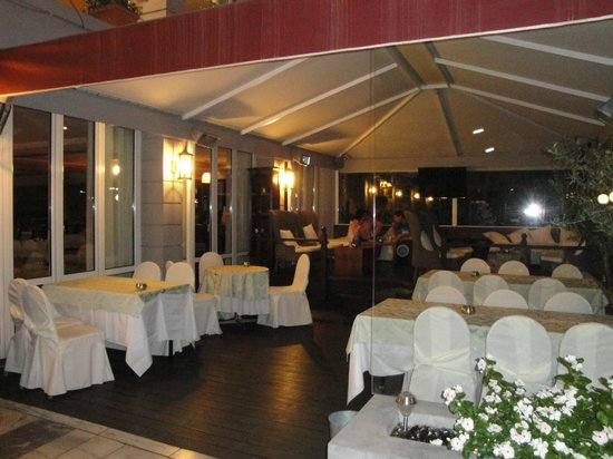 Coral Hotel Athens: Outside dining area at night, this is right before you walk into the hotel lobby