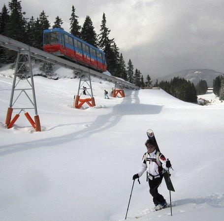 Seefeld in Tirol, Österreich: Risalita con sciettini e snowboard in spalla. Sullo sfondo la cremagliera