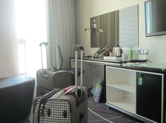 Hotel Verde Cape Town International Airport : Desk with shelves and a mini-fridge.