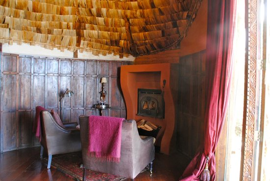andBeyond Ngorongoro Crater Lodge: sitting area and fireplace of room