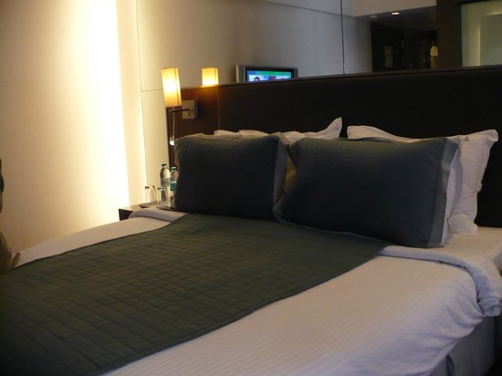 ST LAURN HOTEL, PUNE, KOREGAON PARK: the beds with  refflection on the [arge mirror