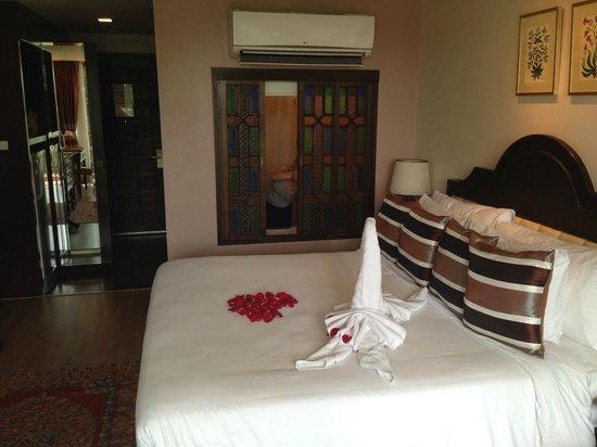 Sheik Istana Hotel: Bed over to wooden bathroom window doors