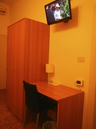Hotel Santa Lucia : Closet, desk, lamp and a mounted tv above