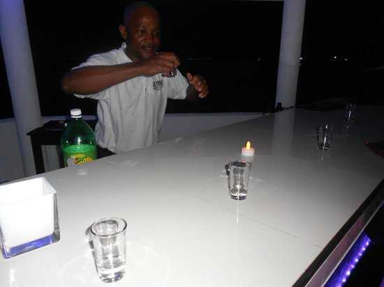 One Love Bus Bar Crawl: Marvin the bartender pouring me a bday shot! & had me dancing on the bar afterwards