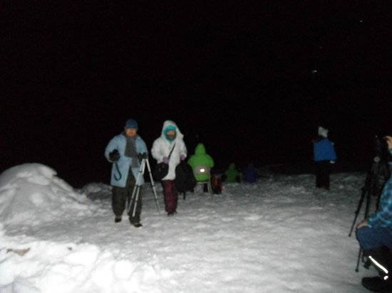 Alaska Northern Lights Tour: Guests are sitting and standing outside waiting for Auroa. A flash pulled  watchers out of the d
