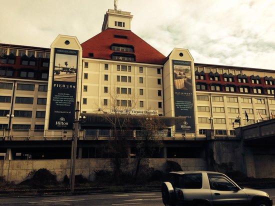 Hilton Vienna Danube Waterfront: Vistas del edificio del hotel, desde el aparcamiento público.