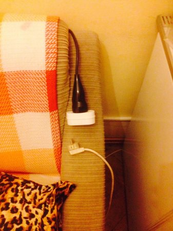 Pension Mozart: Extension lead hanging over the sofa for the fridge which is unplugged with mould! Disgusting!!