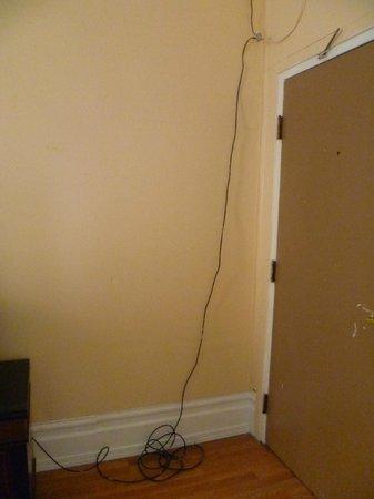 يوروبا هوتل: des fils électriques courent le long de la cloison (à droite la porte d'entrée de la chambre)