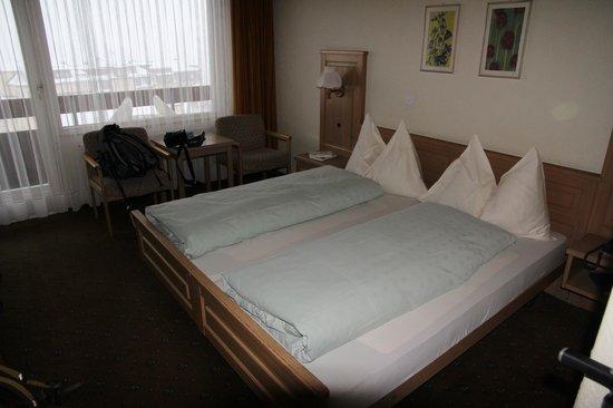 Hotel Restaurant Alpina Grindelwald: bed en zitje; bureau en kasten aan andere kant.