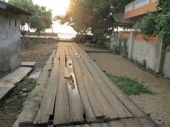 Busua Inn : accès à l'hôtel sur l'égout pestilentiel du village recouvert des planches