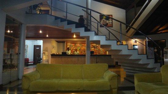 Oceano Praia Hotel: Vista da escada para o 2º piso e recepção com lindo painel de madeira entalhada!