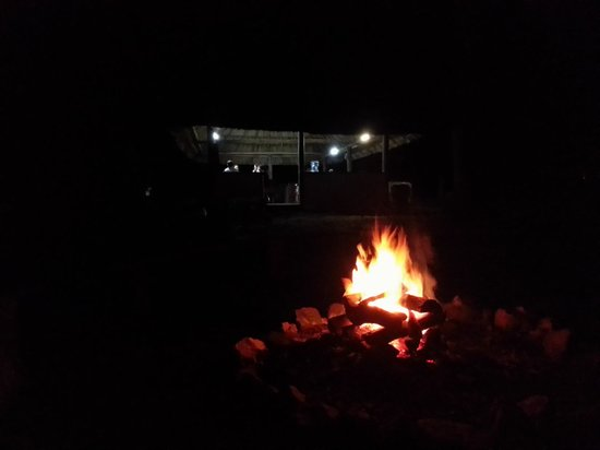 The Lodge at Chaa Creek: bonfire with dining hut in background