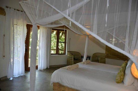 Chobe Bakwena Lodge: mosquito net folded away around bed - every evening we returned to find it fully deployed