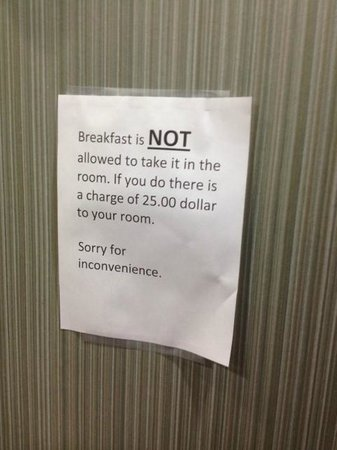 Quality Inn & Suites: Lobby sign - can't take a waffle or anything else back to your room.