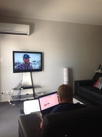 Verandah Apartments Perth: TV in lounge with husband using our own internet as free wifi too slow.