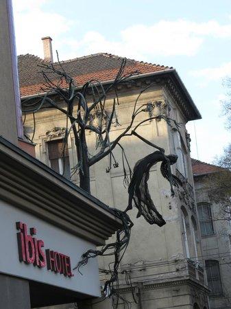 ibis Budapest Heroes Square: Угол отеля и странное украшение в виде дерева с висящей на нем женщиной