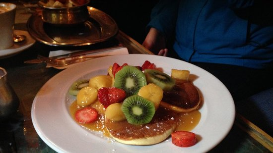 Cafe Clock: Breakfast: pancakes with fried bananas and fresh fruit, topped with caramel sauce.