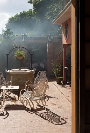 Hostal Maria y Enddy: The barbeque in action, lunch in the arbour visible beyond the chairs, or dinner in the courtyar
