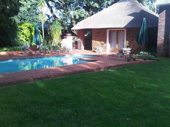 Jameson Country Cottages: View of cottage 1, stone and thatch unit overlooking pool.