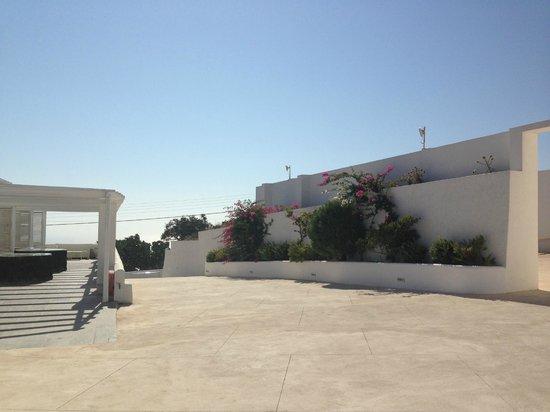 Rocabella Santorini Resort & Spa: Дворик, куда выходят четыре студии, за стеной - корт
