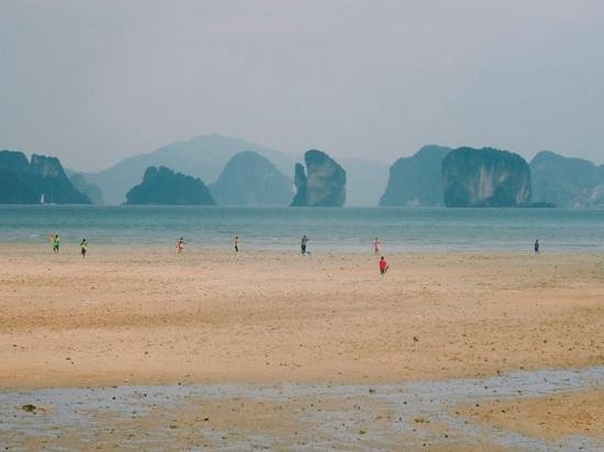 Suntisook Resort: children flying kites on the opposite beach during low tide