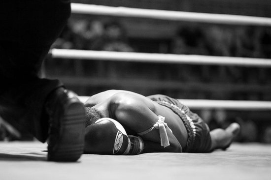 A fighter lying on the canvas after being knocked out