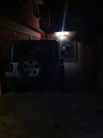 Esperanza Inn: (nighttime) a vehicle parked next to the cinderblock wall to Room 5, no exhaust vent