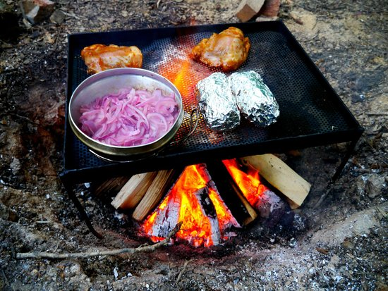 Eco Camp UK - Wild Boar Wood Campsite: dinner cooking on the open fire