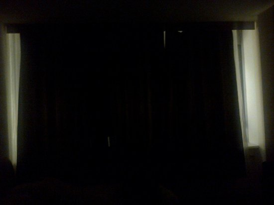 City Hotel Irodion: This is twin room at  night thats the sign shining in with curtains that dont fit window.