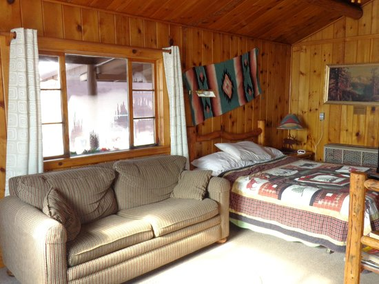 Vista Court Cabins & Lodge: Small sofa and bed, looking out front window