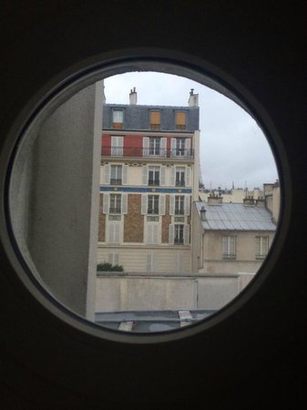 Hotel Jardins d'Eiffel : Peekaboo glimpse of the Eiffel Tower from our port hole window