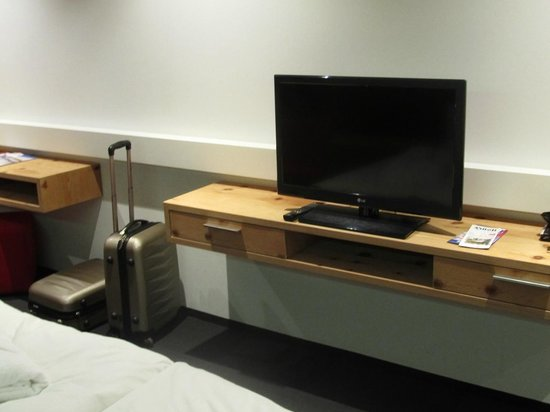 Hotel Tannhof : Ablage mit Schubladen und Fernseher am Fussende des Bettes