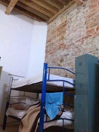 Hostel Casona Poblana: Habitación femenina con pared de ladrillo visto y tirantes de madera