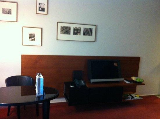 Grand Hyatt Berlin: table et espace télé face au lit