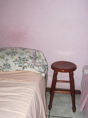 Hotel Ceciliano: Paredes ennegrecidas, aspecto sucio y descuidado. La mesita de noche es un simple taburete.