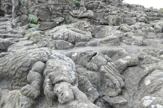 Les Rochers Sculptes: หินสลักบางตัวก็ถูกนํ้าทะเลกัดกร่อนและระยะเวลาที่ล่วงเลยมานานทำให้ดูไม่ชัด