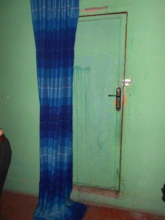 Hostel Riad Marrakech Rouge: porta di compensato scrostata ed inutile come sicurezza