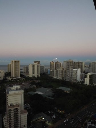 full moon setting from room at Maile sky court hotel