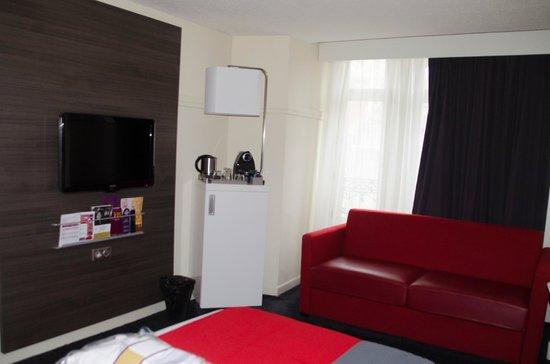 Mercure Lille Centre Grand Place : Petit divan dans la chambre et fenêtre donnant sur le Beffroi