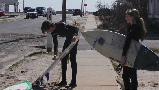 Belmar Beach and Boardwalk: Kids getting there boards ready to surf prior to board walk being repaired after Super Storm San