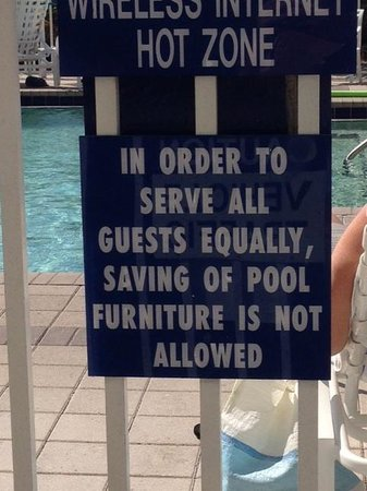 GullWing Beach Resort : Sign at pool saying not to save chairs