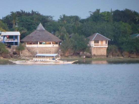 Quo Vadis Dive Resort: round restaurant (left) and single bungalow (right) on waterfront