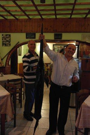 Simos Taverna: Официант Василис держит свежую рыбу-меч, владелец заведения дослеживает за ним)