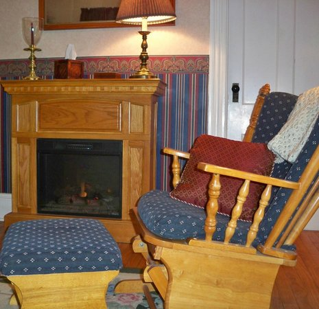 The Inn on Maple Street Bed & Breakfast: Oak room fireplace and rocking chair for relaxation.