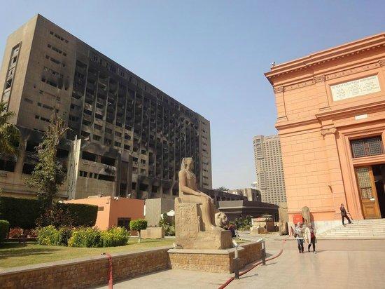 Musée égyptien du Caire : A la derecha, el museo de El Cairo, a la izquierda, la sede del partido de Mubarak quemado
