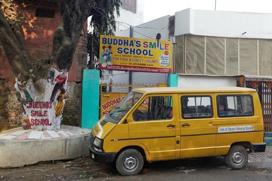Saini Guest House: schoolbus and entrance of the school next to the cafe