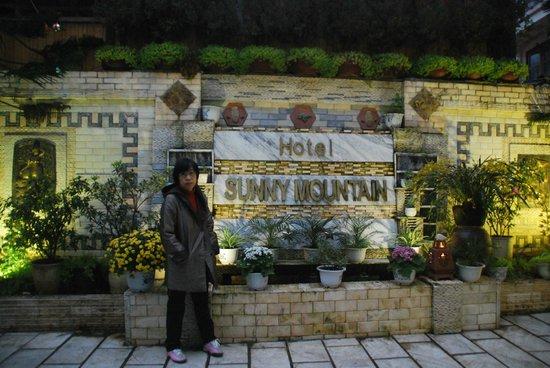 Sunny Mountain Hotel: ทิวทัศน์การจัดสวนที่สวยงามหน้าป้ายโรงแรม