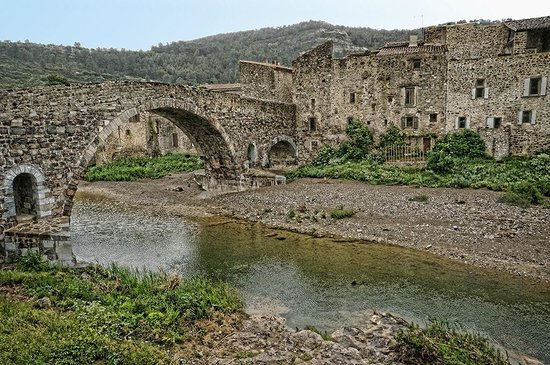 """Abbaye de Lagrasse: A view of the 13th century """"Old Bridge"""" spanning the Orbieu River in Lagrasse"""
