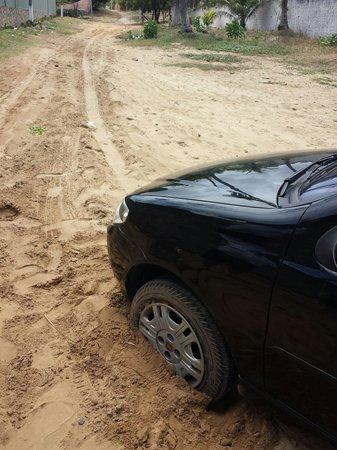 Pousada Furaifun Cumbuco: Nosso carro com as rodas dianteiras atoladas na areia da rua de acesso à pousada. Ausência de ca