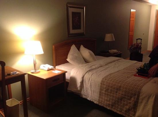 The Grand Hotel Nanaimo: bed, and oak doors seen in the background